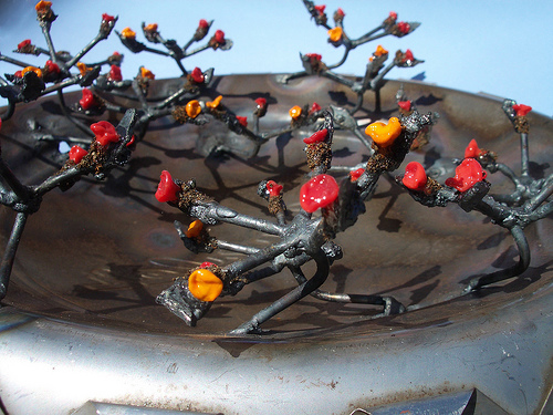 Community-wide project where each artist began with a hubcap to make their piece. Mine used welded steel, steel dust and lampworked glass flowers.