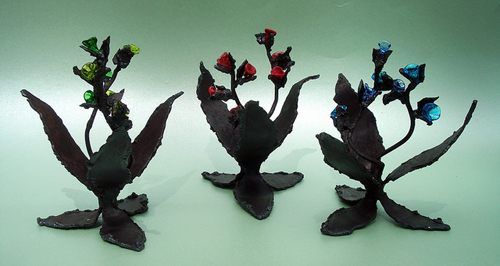 Welded steel plant sculptures with lampworked glass flowers.